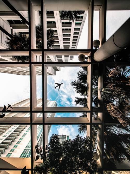 Papel de parede do Avião entre edifícios para celulares e tablets
